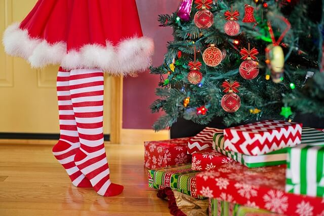 Photo of presents by a tree and a girl reaching | Elf Jokes | Quizzy Kid